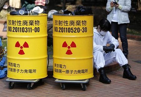 An anti-nuclear protester wearing protective suit sits next to mock drums labelled as radioactive waste from Kansai Electric Power Co's Ohi nuclear power plant (L) and Tokyo Electric Power Co's (TEPCO) Fukushima nuclear power plant, before a march in Tokyo March 9, 2014. REUTERS/Yuya Shino