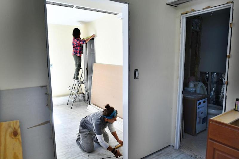 Members of AmeriCorps install a door frame in a house damaged by Hurricane Sandy in Brooklyn in 2017.