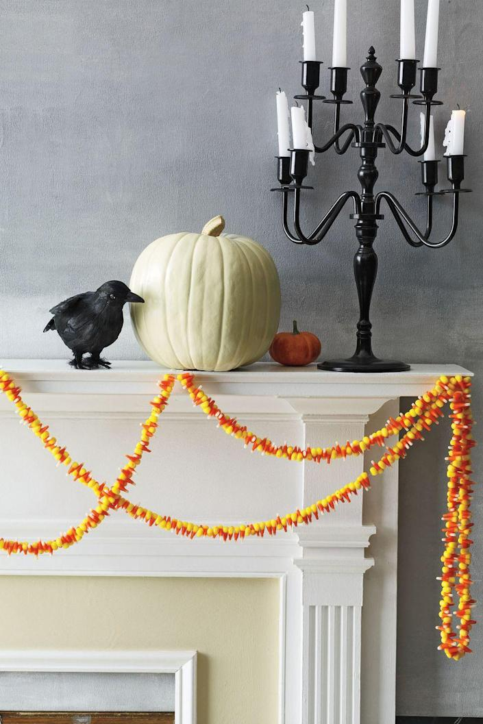 """<p>Garlands aren't just for Christmas! String candy corn onto monofilament fishing line with a needle (just avoid areas where the colors meet — corn can break at those points). Hang on a mantel or a staircase using cloth tape.<strong><br></strong></p><p><strong>RELATED:</strong> <a href=""""https://www.womansday.com/home/crafts-projects/how-to/g332/diy-candy-corn-decorations"""" rel=""""nofollow noopener"""" target=""""_blank"""" data-ylk=""""slk:23 DIY Candy Corn Crafts for Halloween"""" class=""""link rapid-noclick-resp"""">23 DIY Candy Corn Crafts for Halloween</a></p>"""
