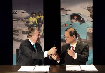 Toll Holdings Ltd Chairman Ray Horsburgh (L) and Japan Post Chief Executive Toru Takahashi exchange a pen during an official signing ceremony in Sydney February 18, 2015.   REUTERS/Jeremy Piper/Oculi