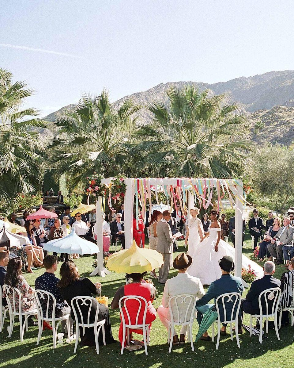 """<p>Opt for color—in a different way. Skip the over-the-top flower installations or wedding arches and go for colorful streamers a la Samira Wiley and Lauren Morelli's ceremony in Palm Springs, CA. Inspired by confetti cake and all things fun, the pair kept their altar carefree, lively, and a reflection of their vibrant, zest for life as individuals, and a couple. </p><p><em>Pictured: Planning by <a href=""""https://www.bethhelmstetter.com/"""" rel=""""nofollow noopener"""" target=""""_blank"""" data-ylk=""""slk:Beth Helmstetter"""" class=""""link rapid-noclick-resp"""">Beth Helmstetter</a>; Florals by <a href=""""http://www.hollyflora.com/"""" rel=""""nofollow noopener"""" target=""""_blank"""" data-ylk=""""slk:Holly Flora"""" class=""""link rapid-noclick-resp"""">Holly Flora</a>. </em></p>"""