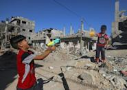 Palestinian children play with toy guns next to the ruins of a house hit by Israeli air strikes earlier this month in Beit Hanoun in the northern Gaza Strip