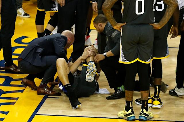 Golden State's Klay Thompson is on the court after suffering a left knee injury following an awkward landing from a shot attempt in the third quarter of game six of the NBA Finals (AFP Photo/Lachlan Cunningham)