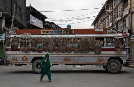 A Kashmiri woman walks past a bus used as a road block by Indian security personnel during restrictions after the scrapping of the special constitutional status for Kashmir by the government, in Srinagar