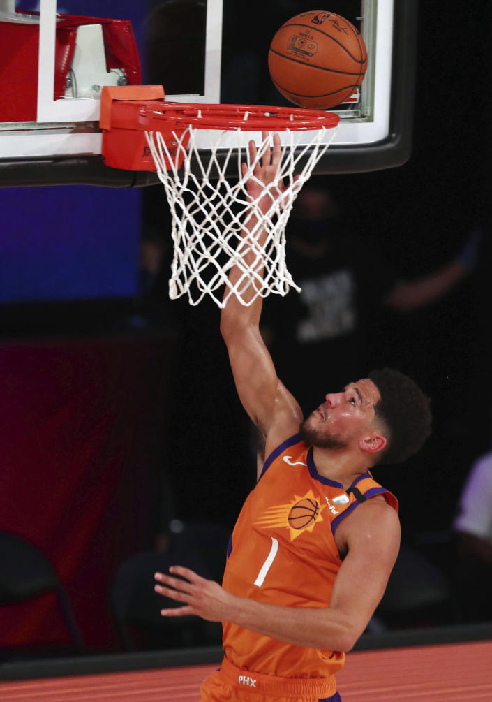 Phoenix Suns guard Devin Booker (1) shoots the ball against the Washington Wizards durin the first half of an NBA basketball game Friday, July 31, 2020, in Lake Buena Vista, Fla. (Kim Klement/Pool Photo via AP)