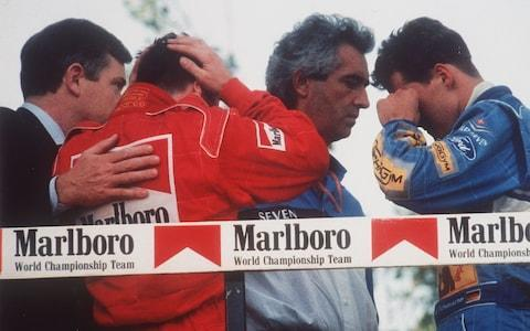 In this May 01, 1994, file photo, Italy's Nicola Larini, left, holds his head and Germany's Michael Schumacher, right, wipes a tear from his eyes while talking with Benetton director-general Flavio Briatore, center, on the podium following the San Marino Formula One Grand Prix crash in Imola, Italy. The drivers were reacting to the news that the Brazilian driver Ayrton Senna was in critical condition at a Bologna hospital after a crash in the race. Later it was announced that Senna had died after suffering severe head injuries. Schumacher won the race and Larini finished second - Credit: AP