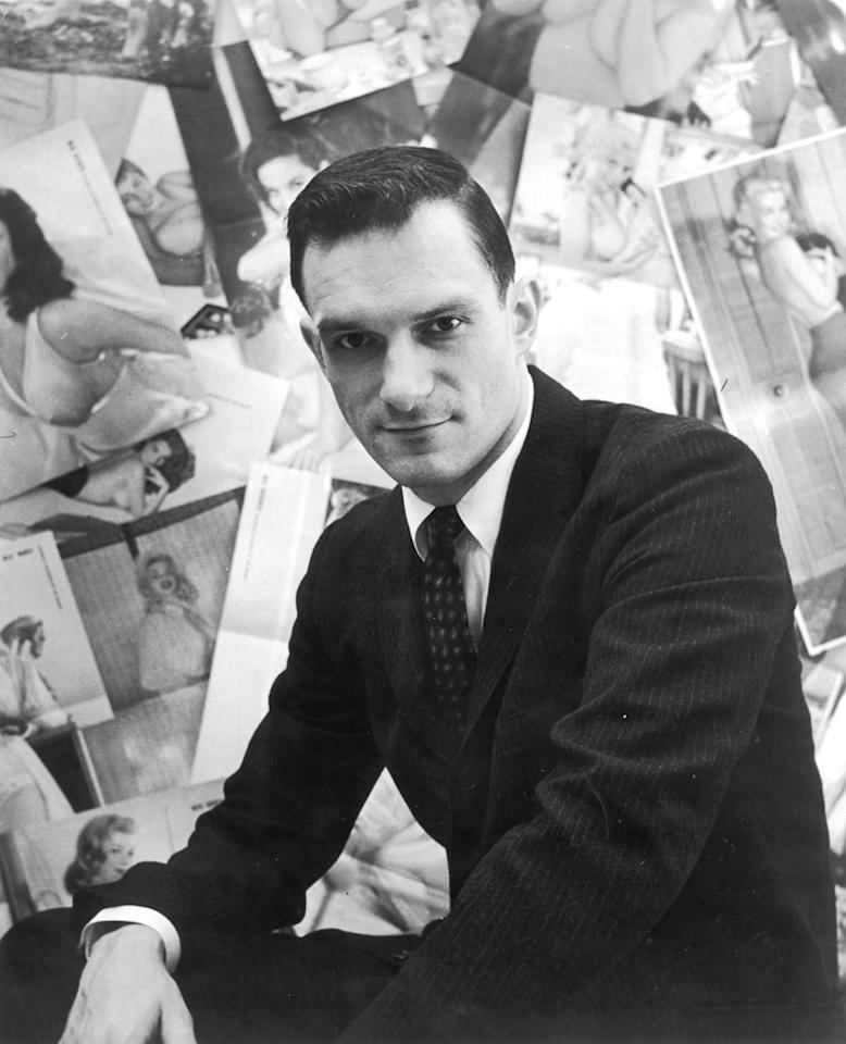 Portrait of American publisher Hugh Hefner sitting in front of a wall collage of female centerfolds from his men's magazine 'Playboy' which he launched in 1953.   (Photo by Archive Photos/Getty Images)