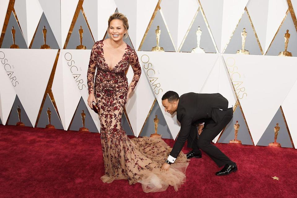 <p>Legend sorts out the train of Teigen's Oscar's dress, being a great husband and fashion assistant.</p>