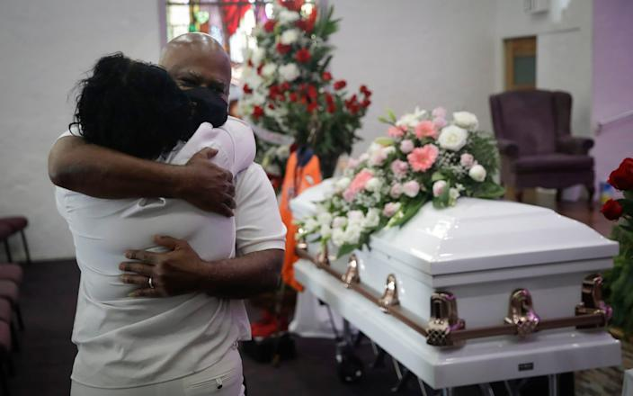 Two relatives hug during a funeral service for Lydia Nunez, who died of Covid-19, at the Metropolitan Baptist Church in Los Angeles - Marcio Jose Sanchez /AP