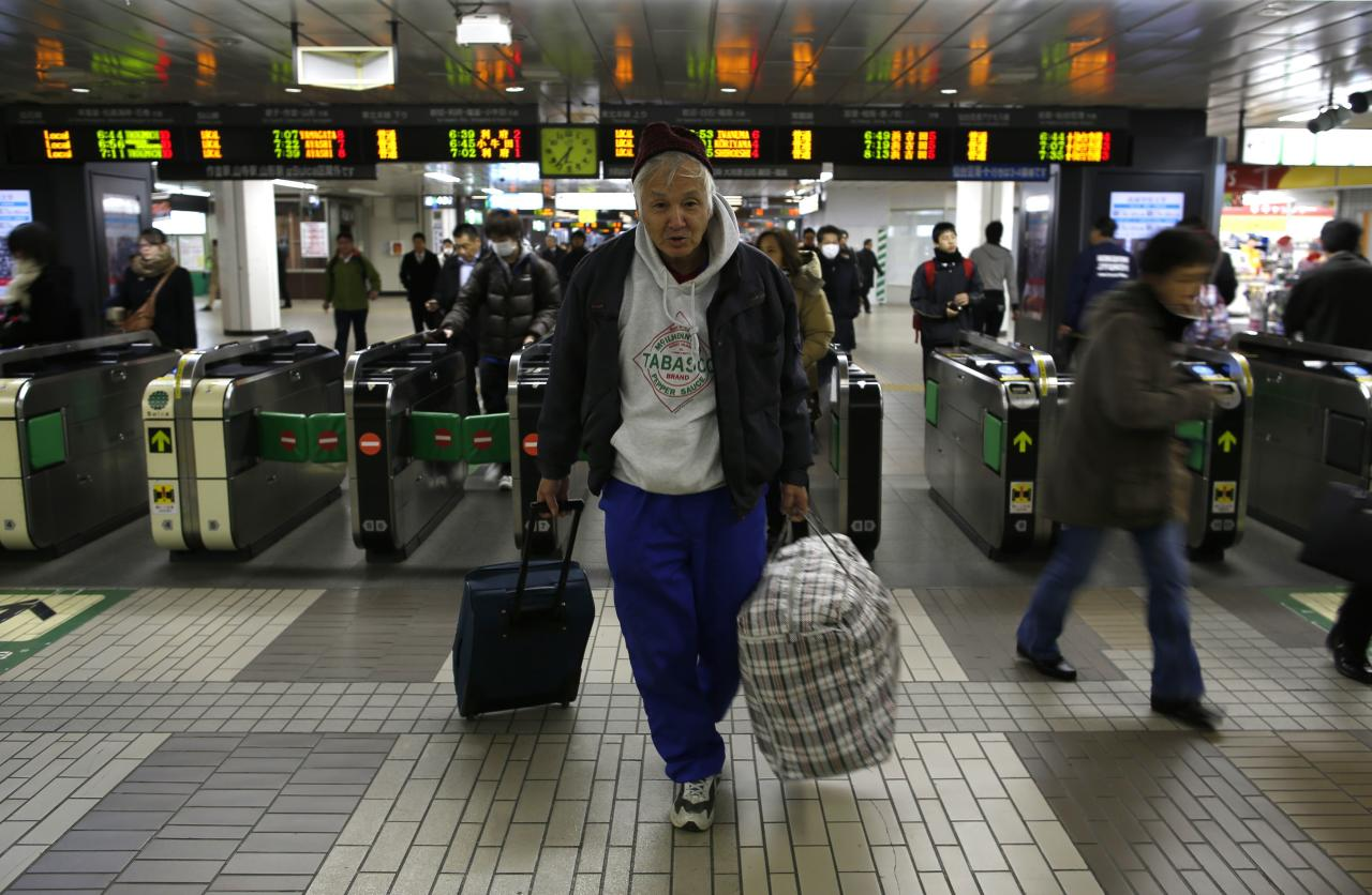 Shizuya Nishiyama (C), a 57-year-old homeless man from Hokkaido, poses for a photo in front of an automatic ticket barrier at Sendai Station in Sendai, northern Japan December 18, 2013. Picture taken December 18, 2013. To match Special Report FUKUSHIMA-WORKERS/ REUTERS/Issei Kato (JAPAN - Tags: CRIME LAW DISASTER BUSINESS EMPLOYMENT CONSTRUCTION POLITICS)