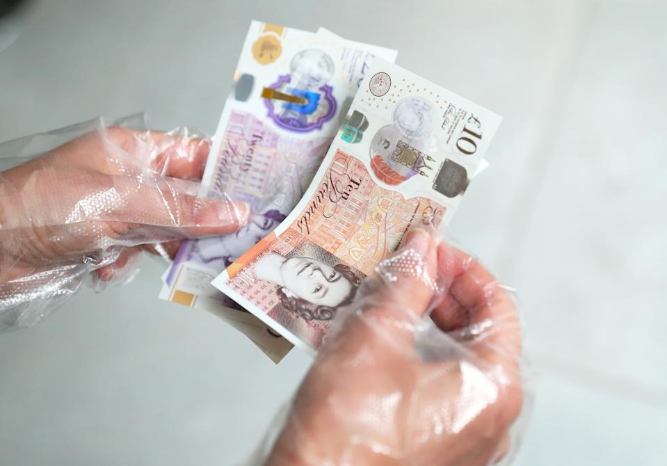 MANCHESTER,  - MARCH 19:   A woman handles banknotes while wearing protective gloves as the UK adjusts to life under the Coronavirus pandemic on March 19, 2020 in Manchester, UK.  (Photo by Alex Livesey - Danehouse/Getty Images)