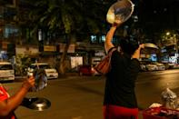 People clatter pans to make noise after calls for protest went out on social media in Yangon on February 3, 2021