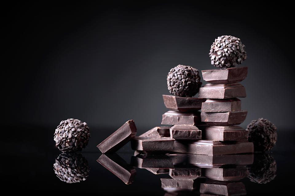 Chocolate candies with broken chocolate pieces on black reflective background. Copy space.
