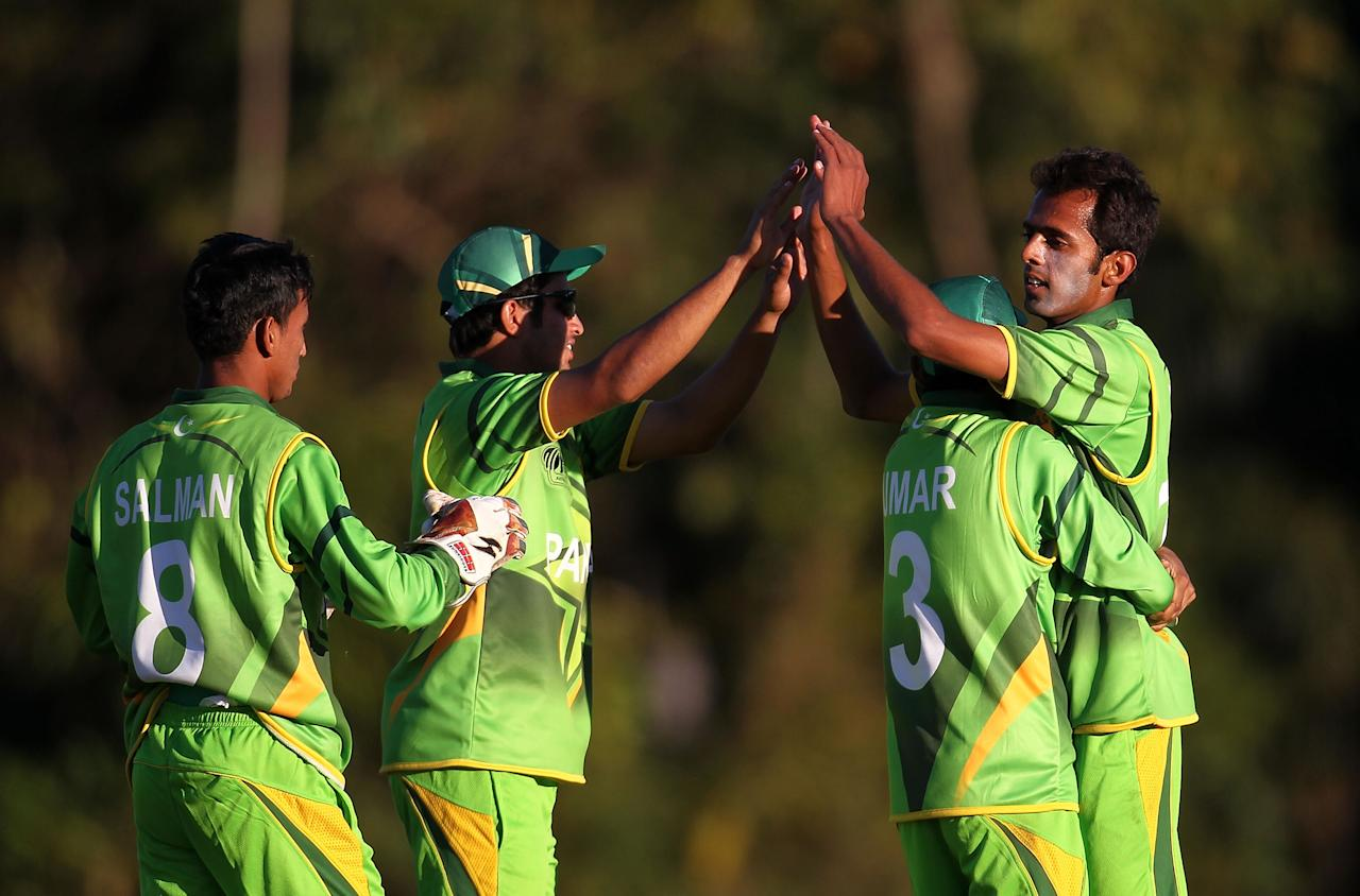 SUNSHINE COAST, AUSTRALIA - AUGUST 11:  Muhammad Zia Ul Haq of Pakistan (R) is embraced by team mates as they celebrate the wicket of Afsar Khann of Afghanistan during the ICC U19 Cricket World Cup 2012 match between Pakistan and Afghanistan at John Blanck Oval on August 11, 2012 in Sunshine Coast, Australia.  (Photo by Graham Denholm-ICC/Getty Images)