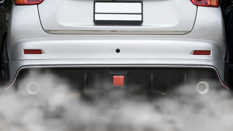 Emission combustion fumes coming out of exhaust pipes