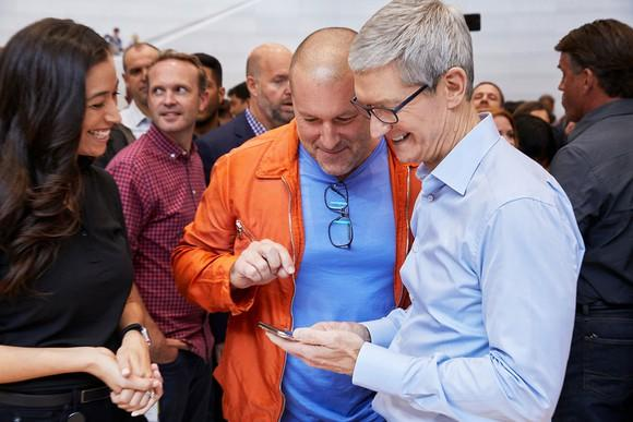 Apple executives Tim Cook and Jony Ive using an iPhone X with smiles on their faces.