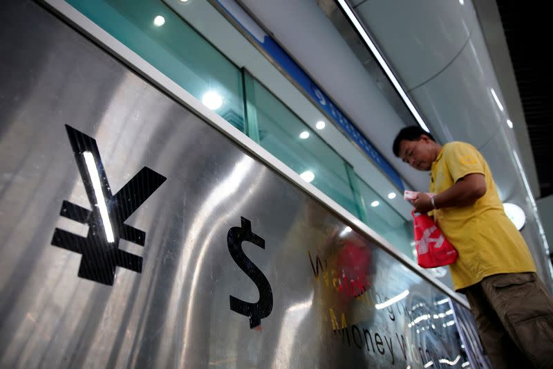 FILE PHOTO: Signs of Chinese yuan and U.S. dollar are seen at a currency exchange store in Shanghai