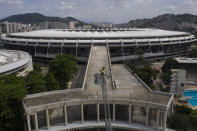 FILE - In this April 5, 2020 file photo, Backdropped by Maracana stadium, firefighter Elielson Silva plays his trumpet from the top of a ladder for residents at home, during a lockdown to help contain the spread of the new coronavirus in Rio de Janeiro, Brazil. (AP Photo/Leo Correa, File)