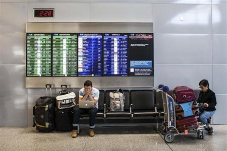 Passengers wait for their delayed flights after an Asiana Airlines Boeing 777 crashed and burst into flames as it landed at San Francisco International Airport