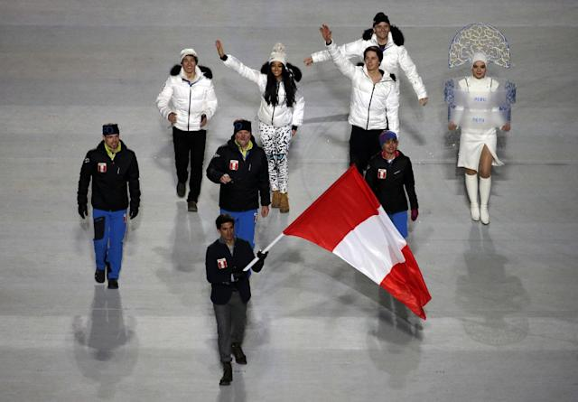Roberto Carcelen of Peru holds his national flag and enters the arena with teammates during the opening ceremony of the 2014 Winter Olympics in Sochi, Russia, Friday, Feb. 7, 2014. (AP Photo/Charlie Riedel)