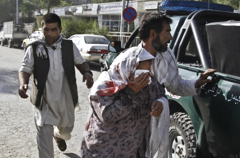 Afghan men rush a wounded woman to receive treatment, after a suicide car bomber struck outside the Afghan Supreme Court in Kabul, Afghanistan, Tuesday, June 11, 2013. The suicide car bomber killed more than a dozen people and wounded at least 30, police and health officials said. The car bomb exploded outside the court's back entrance as employees were leaving for the day and as cars belonging to staff were driving out of the back gate, said police officer Jahn Agha. (AP Photo/Ahmad Jamshid)