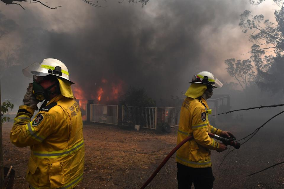Rural Fire Service (RFS) crews douse a home lost to a bushfire on Hassall Road in Buxton as the Green Wattle Creek Fire threatens a number of communities in the southwest of Sydney.