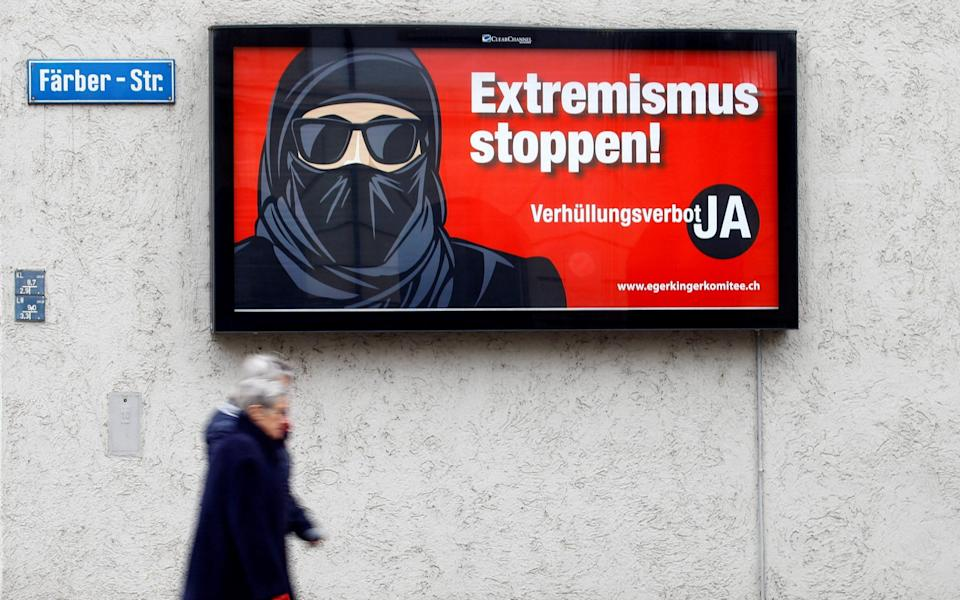 """Pedestrians walk past a campaign poster promoting a 'burka ban'. The poster shows an image of a woman with her face covered alongside the words """"Stop extremism! Veil ban - Yes"""" - REUTERS/Arnd Wiegmann"""