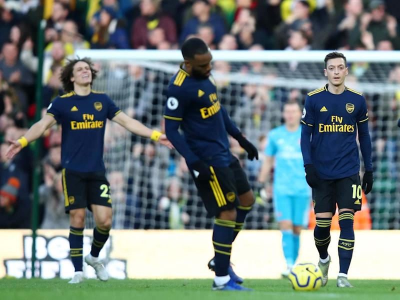 Mesut Ozil of Arsenal and teammates walk back to the half way line: Getty