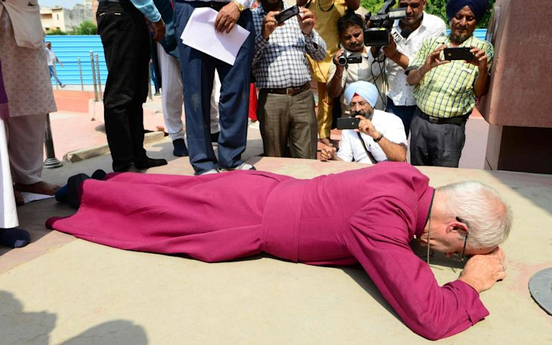 Justin Welby prostrated himself in a gesture of apology - AFP