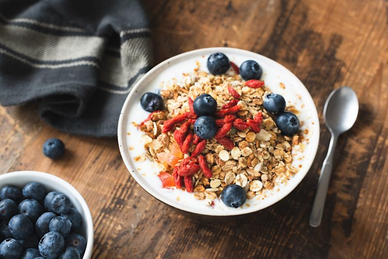 Granola bowl with yogurt, blueberries and goji berries on old wooden table. Healthy vegetarian eating, healthy lifestyle concept