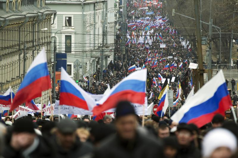 More than ten thousand pro-Kremlin demonstrators many holding Russian flags march in central Moscow, Russia, Sunday, March 2, 2014 to express support for the latest developments in Russian-Ukrainian relations. (AP Photo/Pavel Golovkin)