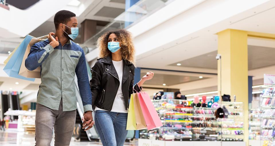 African american loving couple in protective face masks spending time together after shopping in mall center, panorama with free space. Black man and woman walking by shopping mall during quarantine