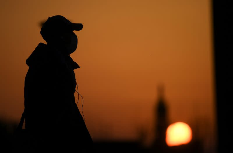 A person wearing a face mask is seen at the sunset as the spread of coronavirus disease (COVID-19) continues, in Milan