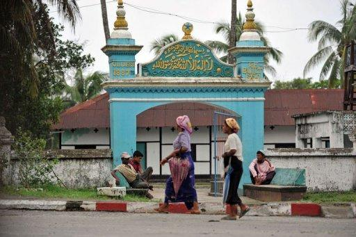 Muslim women walk past a mosque in Sittwe, capital of Myanmar's western Rakhine state, on June 6, 2012. Despite generations as part of the religious fabric of the country Muslims are considered foreigners in Buddhist-majority Myanmar, where tensions spilled into deadly violence this week