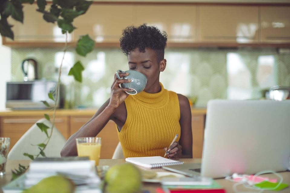 Young woman is drinking and making a budget