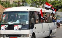 Pictures of Syrian President Bashar al Assad are seen on a bus in Beirut