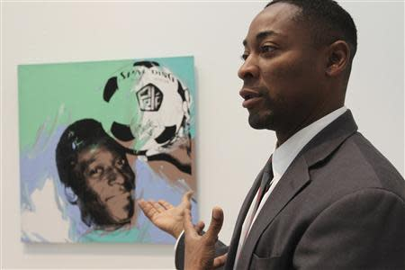 """Curator Franklin Sirmans stands next to """"Pele"""" by Andy Warhol during construction of the exhibition, """"Futbol: The Beautiful Game"""", at the Los Angeles County Museum of Art (LACMA) in Los Angeles, California, January 27, 2014. REUTERS/David McNew"""