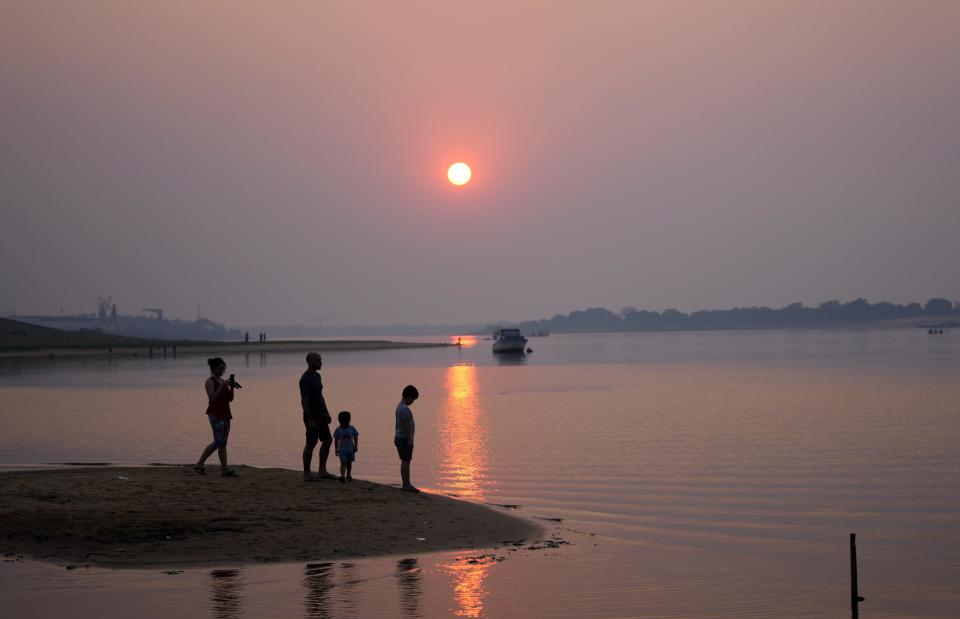 A family is silhouetted against a reddish sunset caused by countryside fires in Asuncion, Paraguay, Saturday, Aug. 21, 2021. (AP Photo/Jorge Saenz)
