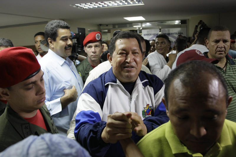 Venezuela's President Hugo Chavez, center, greets supporters during a visit to injured people during a refinery explosion at the Rafael Calle Sierra's public hospital in Punto Fijo, Venezuela, Monday, Aug. 27, 2012. A fire at the Amuay refinery spread to a third fuel tank on Monday nearly three days after a powerful explosion that killed 41 people and ignited the blaze, Vice President Elias Jaua said. Second from left, Venezuela's Foreign Minister Nicolas Maduro. (AP Photo/Ariana Cubillos)