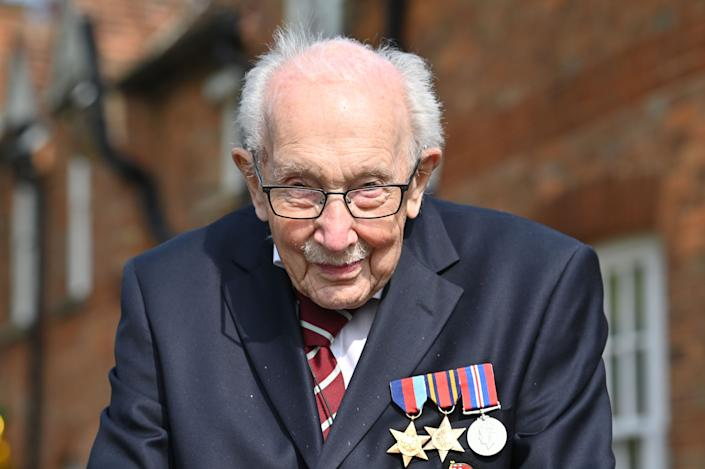 """British World War II veteran Captain Tom Moore, 99, poses doing a lap of his garden in the village of Marston Moretaine, 50 miles north of London, on April 16, 2020. - A 99-year-old British World War II veteran Captain Tom Moore on April 16 completed 100 laps of his garden in a fundraising challenge for healthcare staff that has """"captured the heart of the nation"""", raising more than £13 million ($16.2 million, 14.9 million euros). """"Incredible and now words fail me,"""" Captain Moore said, after finishing the laps of his 25-metre (82-foot) garden with his walking frame. (Photo by JUSTIN TALLIS / AFP) (Photo by JUSTIN TALLIS/AFP via Getty Images)"""