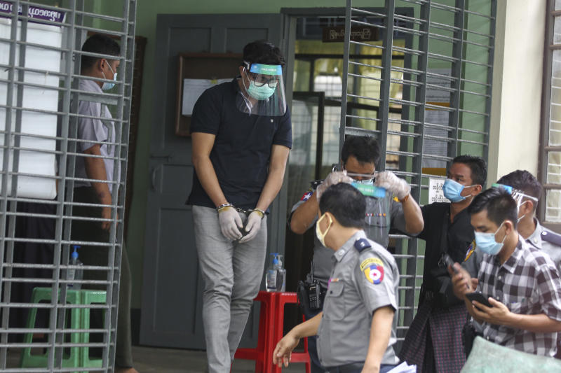 Canadian pastor David Lah cuffed wearing face shield and mask is escorted by police as he leaves from a township court after his first appearance Wednesday, May 20, 2020, in Yangon, Myanmar. Lah attends a court hearing related to charges filed against him for allegedly organizing public Christian activities in Yangon back in April, after the regional government banned mass gatherings in mid-March to curb the spread of the coronavirus. (AP Photo/Thein Zaw)
