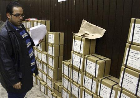 An election official stands next to boxes containing voting slips for a referendum on the new constitution in Cairo