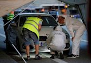 Police forensic experts work on a car where a 21-year-old Syrian refugee killed a woman with a machete and injured two other people in the city of Reutlingen, Germany July 24, 2016. REUTERS/Vincent Kessler