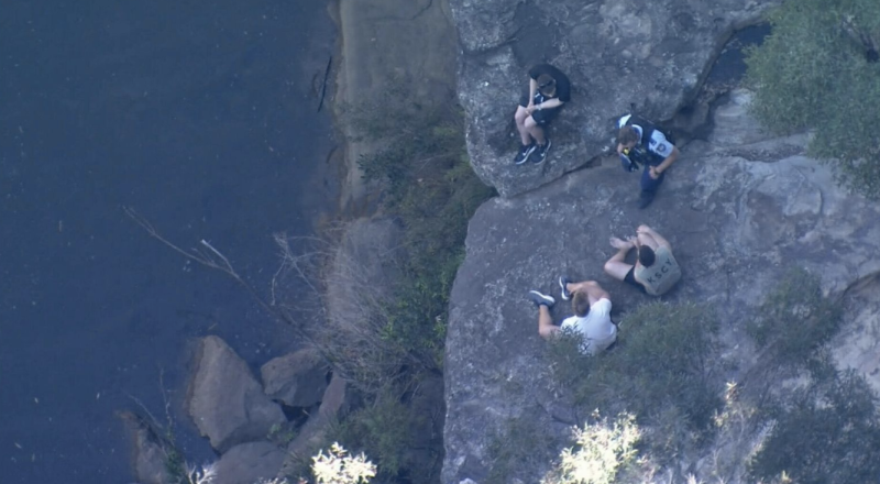 The boy's friend's can be seen watching the rescue. Source: Nine News