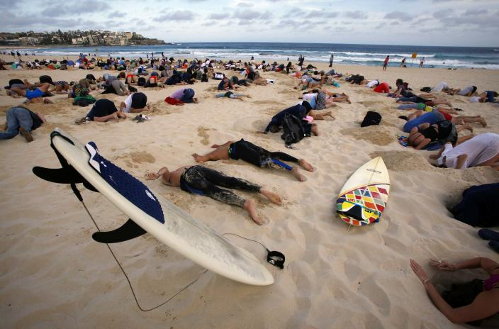 """A group of around 400 demonstrators participate in a protest by burying their heads in the sand at Sydney's Bondi Beach November 13, 2014. Hundreds of protesters participated in the event, held ahead of Saturday's G20 summit in Brisbane, which was being promoted as a message to Australian Prime Minister Tony Abbott�s government that, """"You have your head in the sand on climate change"""". REUTERS/David Gray (AUSTRALIA - Tags: POLITICS CIVIL UNREST SOCIETY ENVIRONMENT)"""