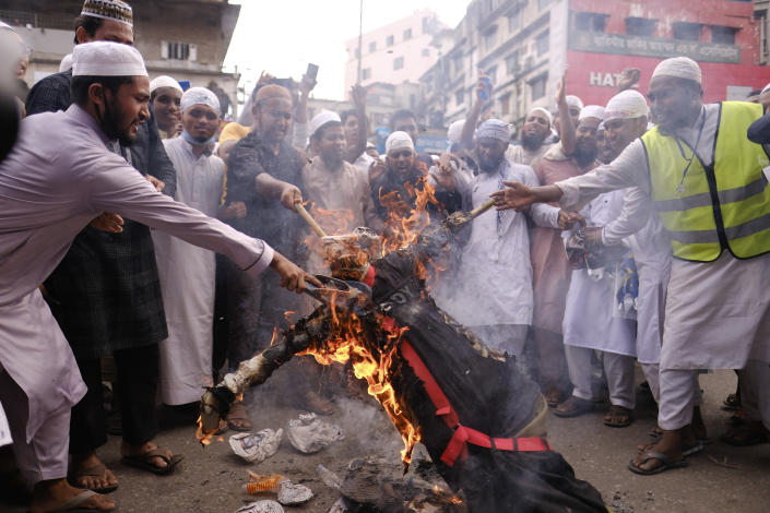 Bangladeshi Muslims protesting the French president's support of secular laws allowing caricatures of the Prophet Muhammad march burn an effigy of French President Emmanuel Macron in Dhaka, Bangladesh, Monday, Nov.2, 2020. (AP Photo/Mahmud Hossain Opu)