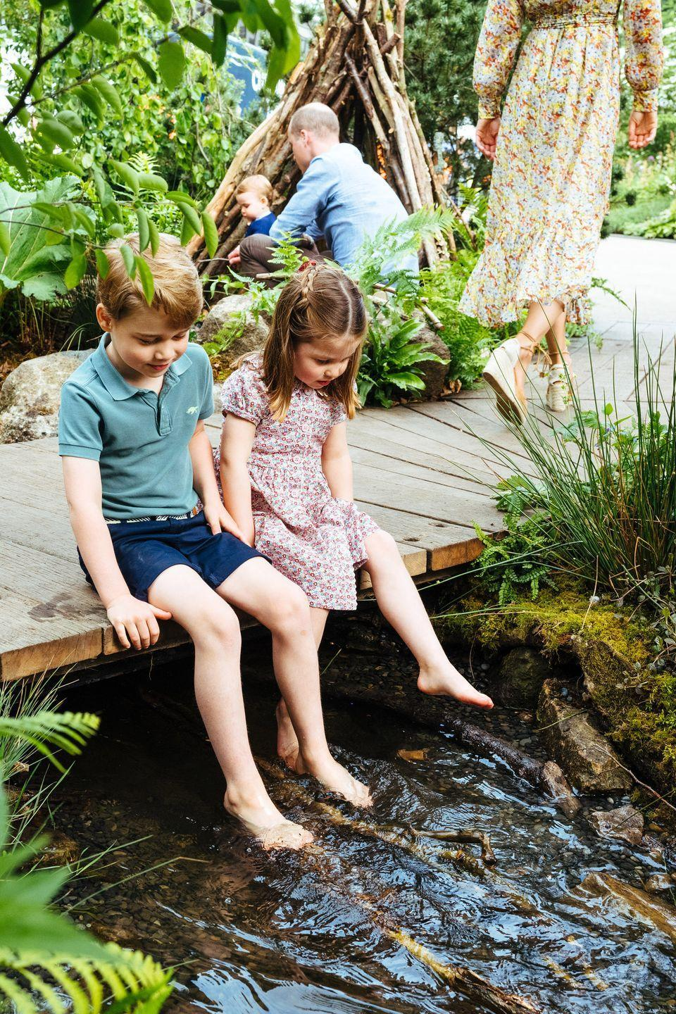 <p>Prince George and Princess Charlotte dip their feet in a stream running through the garden. </p>