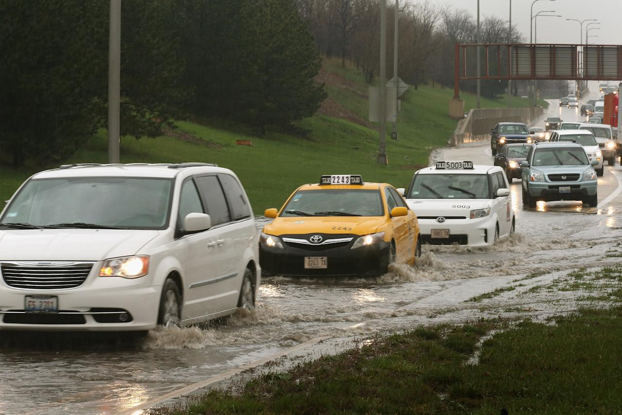 CHICAGO, IL - APRIL 18:  Motorists drive through water on a flooded exit ramp from the Kennedy Expressway on April 18, 2013 in Chicago, Illinois. Thunderstorms dumped up to 5 inches of rain on parts of the Chicago area overnight, closing sections the Edens, Eisenhower and Kennedy expressways, which lead to and from downtown, during the morning rush.  (Photo by Scott Olson/Getty Images)