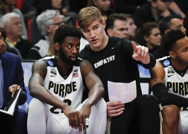 Purdue forward Jacquil Taylor, left, listens to Isaac Haas on the bench against Butler during the first half of an NCAA men's college basketball tournament second-round game in Detroit, Sunday, March 18, 2018. (AP Photo/Paul Sancya)