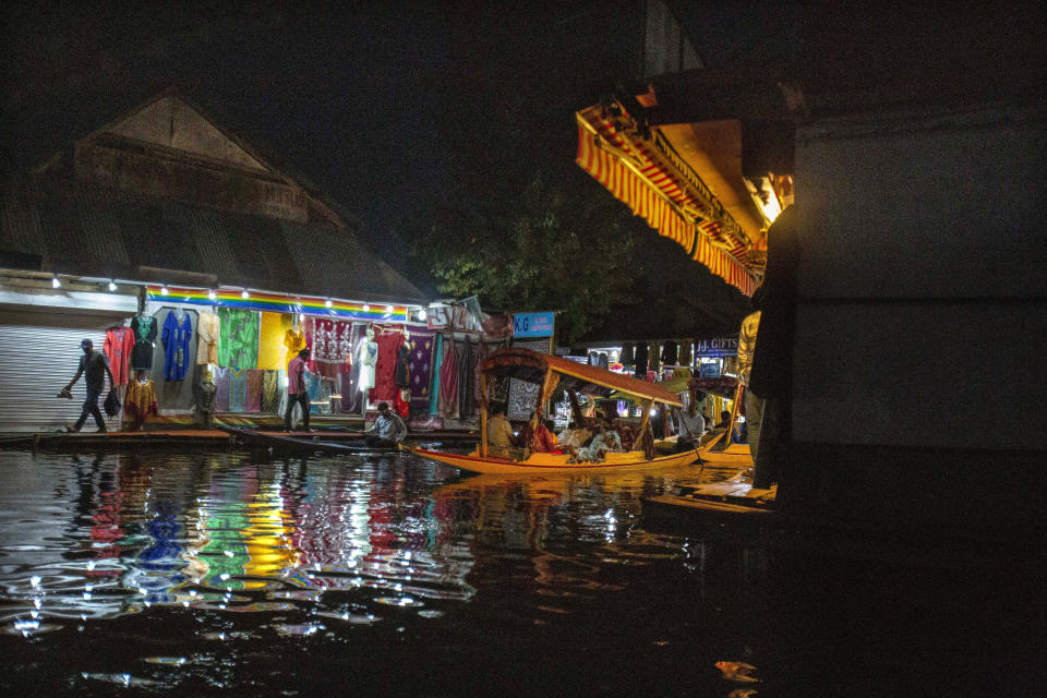 A Kashmiri boatman rows his boat carrying Indian tourists at a market in the interior of Dal Lake in Srinagar, Indian controlled Kashmir, Monday, Aug. 2, 2021. Dal Lake appears pristine in the area where hundreds of exquisitely decorated houseboats bob on its surface for rent by tourists and honeymooners. But farther from shore, the lake is a mixture of mossy swamps, thick weeds, trash-strewn patches and floating gardens made from rafts of reeds. (AP Photo/Mukhtar Khan)